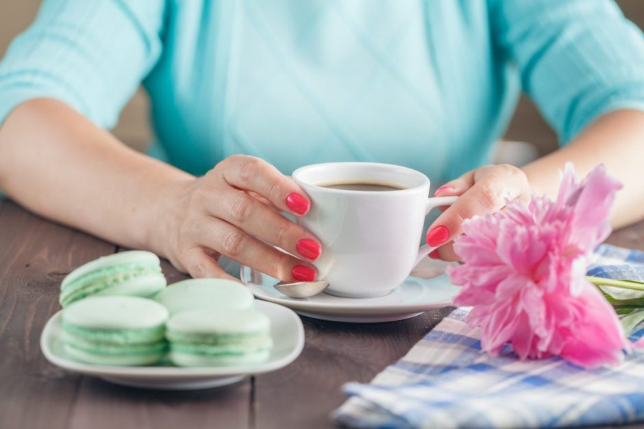 Female hands holding colorful french macaroons