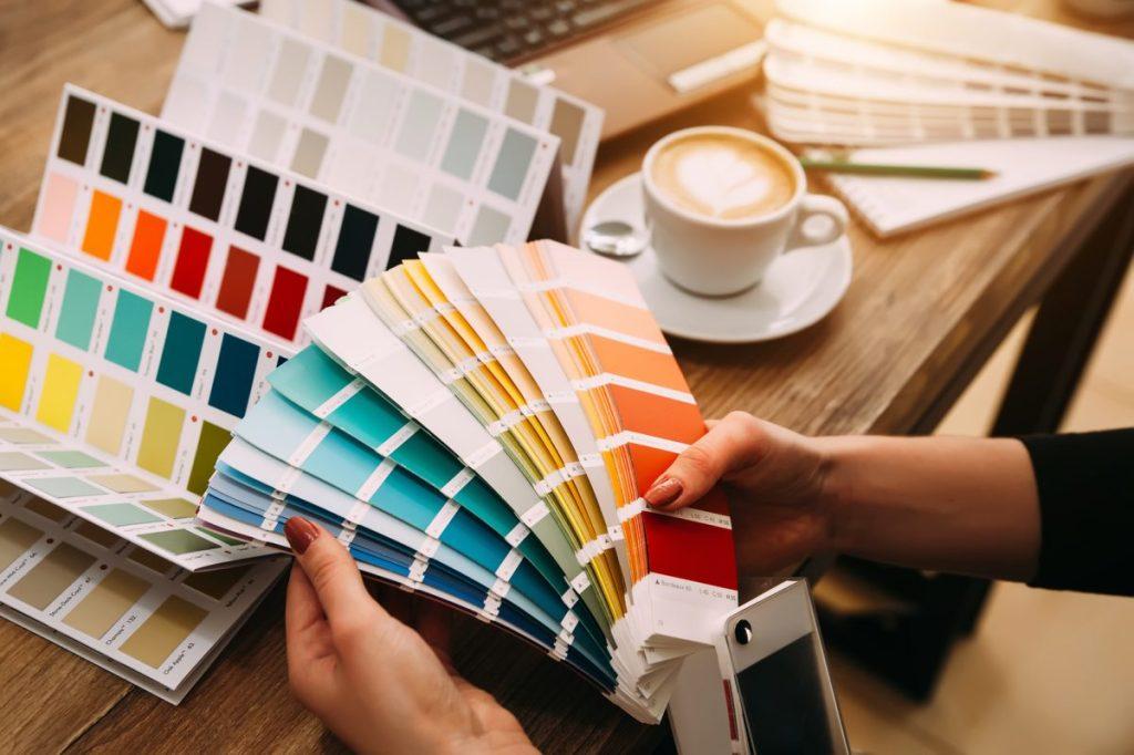 projektant trzyma w dłoniach wzornik kolorów i dobiera kolory w marketingu